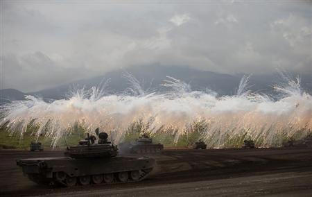 Japanese Ground Self-Defense Force armoured tanks fire during an annual training session near Mount Fuji at Higashifuji training field in Gotemba, west of Tokyo, August 20, 2013. REUTERS/Yuya Shino