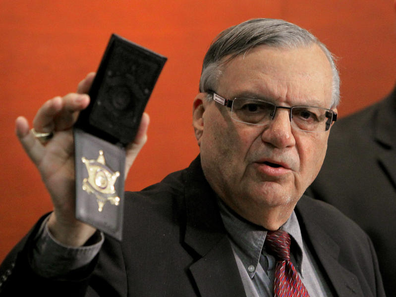 Maricopa County Sheriff Joe Arpaio shows his badge as he holds a ceremony where 92 of his immigration jail officers, who lost their federal power to check whether inmates are in the county illegally, turn in their credentials after federal officials pulled the Sheriff's office immigration enforcement powers Wednesday, Dec. 21, 2011, in Phoenix. The U.S. Department of Homeland Security stripped Sheriff Joe Arpaio's jail officers of their federal powers after federal authorities accused the sheriff's office last week of a wide range of civil rights violations. (AP Photo/Ross D. Franklin)