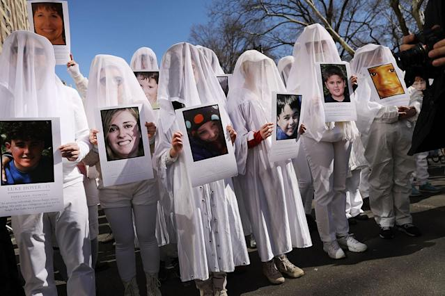<p>People holding pictures of victims killed in gun violence in Manhattan. (Photo: Spencer Platt/Getty Images) </p>
