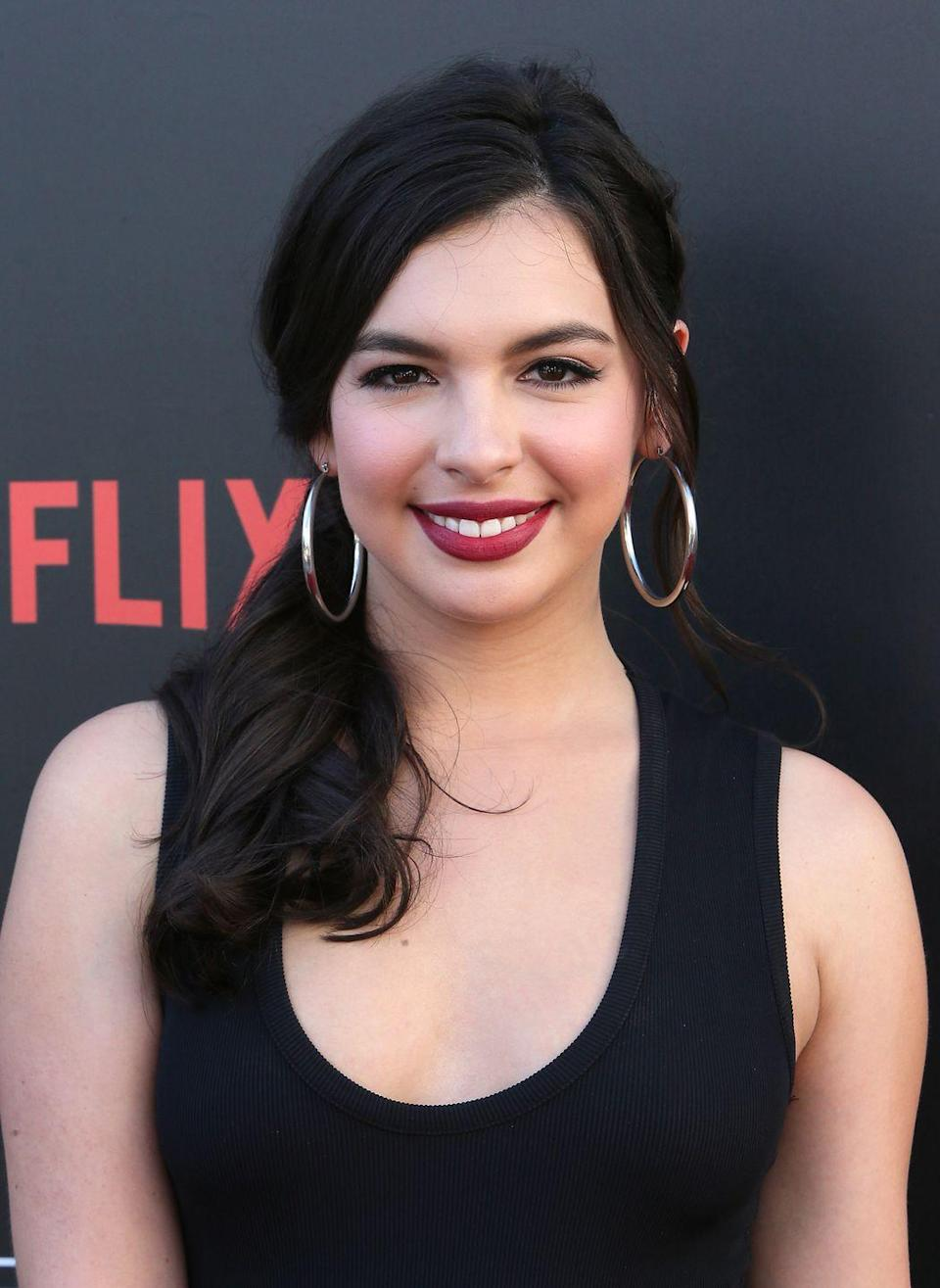 <p>If her hair is on longer side, try pulling her low ponytail over one side of her shoulder. Don't forget to use bobby pins to secure the hair along the nape of her neck — like <strong>Isabella Gomez</strong> from <em>One Day at a Time</em>!</p>