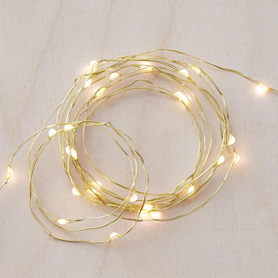 """<p>These <product href=""""https://www.crateandbarrel.com/twinkle-gold-10-string-lights/s365616"""" target=""""_blank"""" rel=""""nofollow"""" class=""""ga-track"""" data-ga-category=""""internal click"""" data-ga-label=""""https://www.crateandbarrel.com/twinkle-gold-10-string-lights/s365616"""" data-ga-action=""""body text link"""">Twinkle Gold String Lights</product> ($13) will liven up your living room.</p>"""