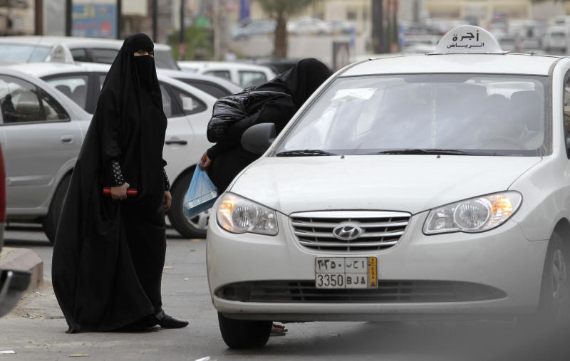 FILE - In this file photo taken Tuesday, May 24, 2011, Saudi women board a taxi in Riyadh, Saudi Arabia. A campaign calling on women to drive on Saturday, Oct. 26, 2013, has started gathering support online and already has nearly 15,000 signatures. (AP Photo/Hassan Ammar, File)