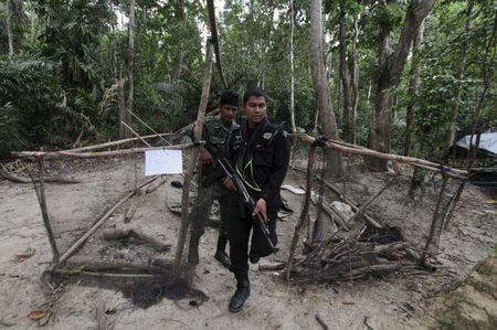 Security forces inspect an abandoned camp at a rubber plantation near a mountain in Thailand's southern Songkhla province May 7, 2015. REUTERS/Surapan Boonthanom