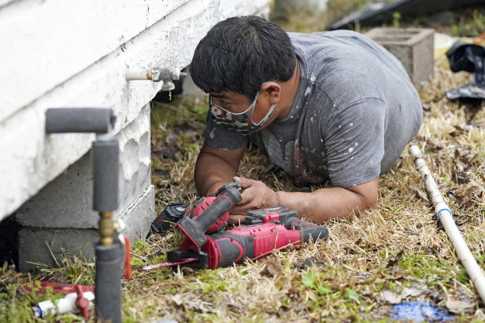 Martin Uribe, with West Street Recovery, works to repair busted pipes under a home, that were frozen during a recent winter storm, Thursday, Feb. 25, 2021, in Houston. West Street Recovery, a nonprofit created in the wake of Hurricane Harvey to help repair flood damaged homes, has been working since the winter storm hit to repair and replace damaged plumbing systems for residents who can't afford to do so. (AP Photo/David J. Phillip)