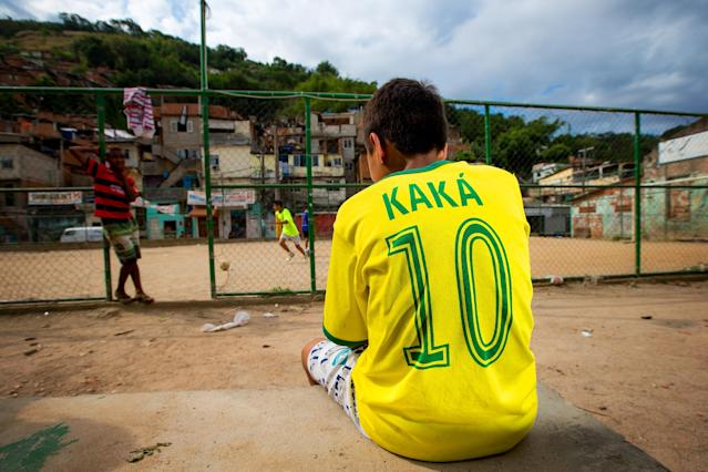 RIO DE JANEIRO, BRAZIL - OCTOBER 26: A young boy wears the jersey bearing the name of the Brazilian team player Kaka while watching a match at the Vila Nova Project in the Morro dos Macacos area on October 26, 2013 in Rio de Janeiro, Brazil. The Project Vila Nova was idealized by Alex Sandro and has so far run for 2 years, catering to children and young residents of the Morro dos Macacos area. (Photo by Buda Mendes/Getty Images)
