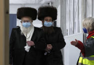 Two men from the Haredi Orthodox Jewish community arrive at an event to encourage vaccine uptake in Britain's Haredi community at the John Scott Vaccination Centre in London, Saturday, Feb. 13, 2021. The event aims to breakdown some of the misconceptions about vaccines, as well as myths and negative publicity surrounding the Haredi community which has been hard hit during the COVID-19 pandemic. (AP Photo/Frank Augstein)