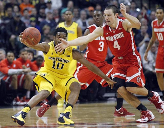 Michigan guard Derrick Walton Jr. (10) and Ohio State guard Aaron Craft (4) chase after a loose ball in the first half of an NCAA college basketball game in the semifinals of the Big Ten Conference tournament Saturday, March 15, 2014, in Indianapolis. (AP Photo/Kiichiro Sato)