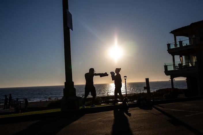 """A man and woman work out with boxing gear near Bruce's Beach in Manhattan Beach on Thursday. <span class=""""copyright"""">(Jay Clendenin / Los Angeles Times)</span>"""