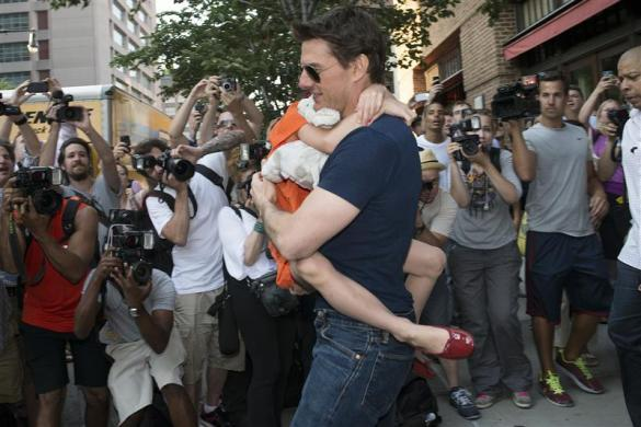 Tom Cruise, $75 million: Tom Cruise carries his daughter Suri past a group of photographers as they make their way from a hotel in New York, July 17, 2012.