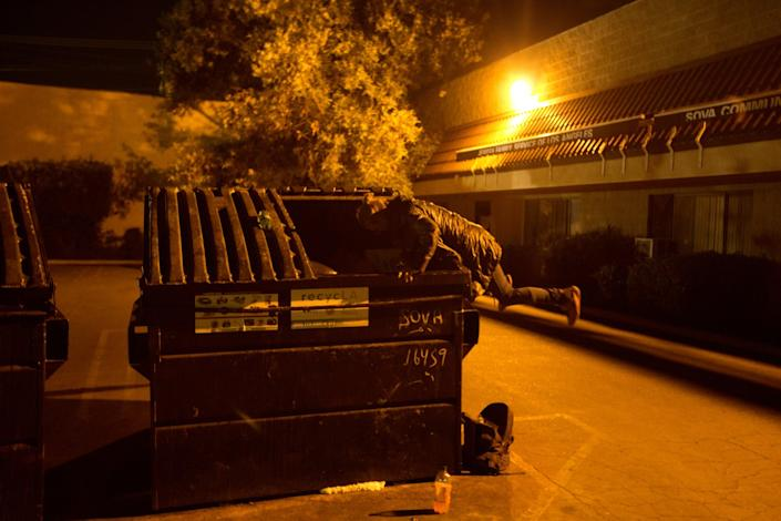 "Elizabeth Bolton looks for food in a dumpster in Van Nuys in April 2019. Bolton said she came to Los Angeles with a traveling circus, split up with the man she came with and ended up living in a homeless community beside the L.A. River, addicted to crystal meth. <span class=""copyright"">(Ivan Kashinsky / For The Times)</span>"