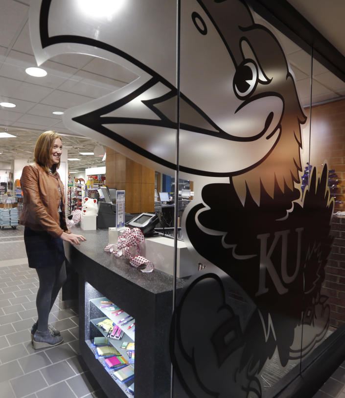 This photo taken Nov. 26, 2013 shows Jane Mahoney standing at a counter in the KU Bookstore on the University of Kansas campus in Lawrence, Kansas. About 320 colleges and universities offered tuition guarantees during the 2012-13 school year, according to an analysis of U.S. Department of Education data done by the National Association of Student Financial Aid Administrators. The schools represent about 6.7 percent of the nation's nearly 4,800 institutions where students receive federal financial aid.Tuition rates for freshmen are guaranteed for four years at Kansas. (AP Photo/Orlin Wagner)