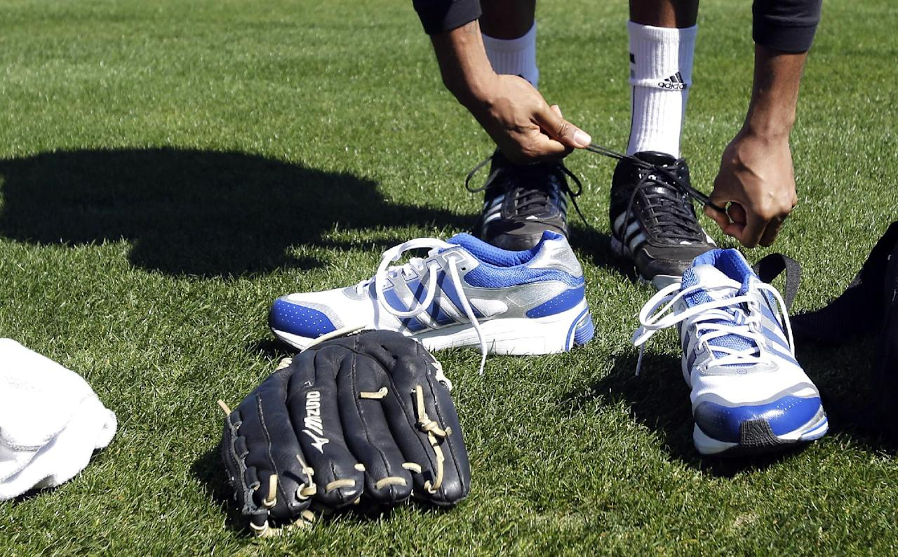 Retired NBA All-Star Tracy McGrady trades his tennis shoes for cleats before a workout at the Sugar Land Skeeters baseball stadium Wednesday, Feb. 12, 2014, in Sugar Land, Texas. McGrady hopes to tryout as a pitcher for the independent Atlantic League Skeeters. (AP Photo/Pat Sullivan)