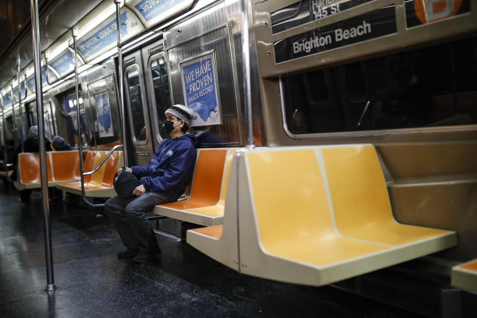 A commuter wears a face mask while riding a nearly empty subway car on March 12, 2020, in New York City. (AP Photo/John Minchillo)