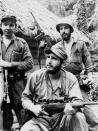 FILE - In this March 14, 1957 file photo, Fidel Castro, the young anti-Batista guerrilla leader, center, stands with his brother Raul Castro, front, and Camilo Cienfuegos, while operating in the mountains of eastern Cuba. For most of his life, Raul Castro played second-string to his brother, but for the past decade, it's Raul who's been the face of communist Cuba. On Friday, April 16, 2021, Raul Castro formally announced he'd step down as head of the Communist Party, leaving Cuba without a Castro in an official position of command for the first time in more than six decades. (AP Photo/Andrew St. George, File)