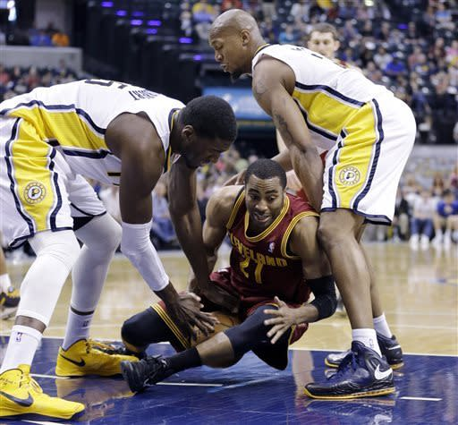 Cleveland Cavaliers guard Wayne Ellington, center, hits the floor for a loose ball between Indiana Pacers center Roy Hibbert, left, and forward David West in the first half of an NBA basketball game in Indianapolis, Tuesday, April 9, 2013. (AP Photo/Michael Conroy)