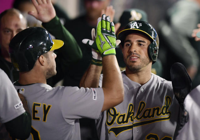 Oakland Athletics' Ramon Laureano, right, is congratulated by Josh Phegley, left, after scoring during the fourth inning of the team's baseball game against the Los Angeles Angels on Thursday, June 6, 2019, in Anaheim, Calif. (AP Photo/Mark J. Terrill)