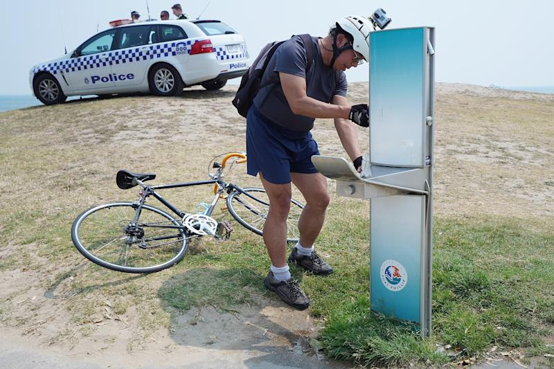 A cyclist fills up his water bottle while police watch over the public cooling down on St Kilda beach during hot weather in Melbourne.