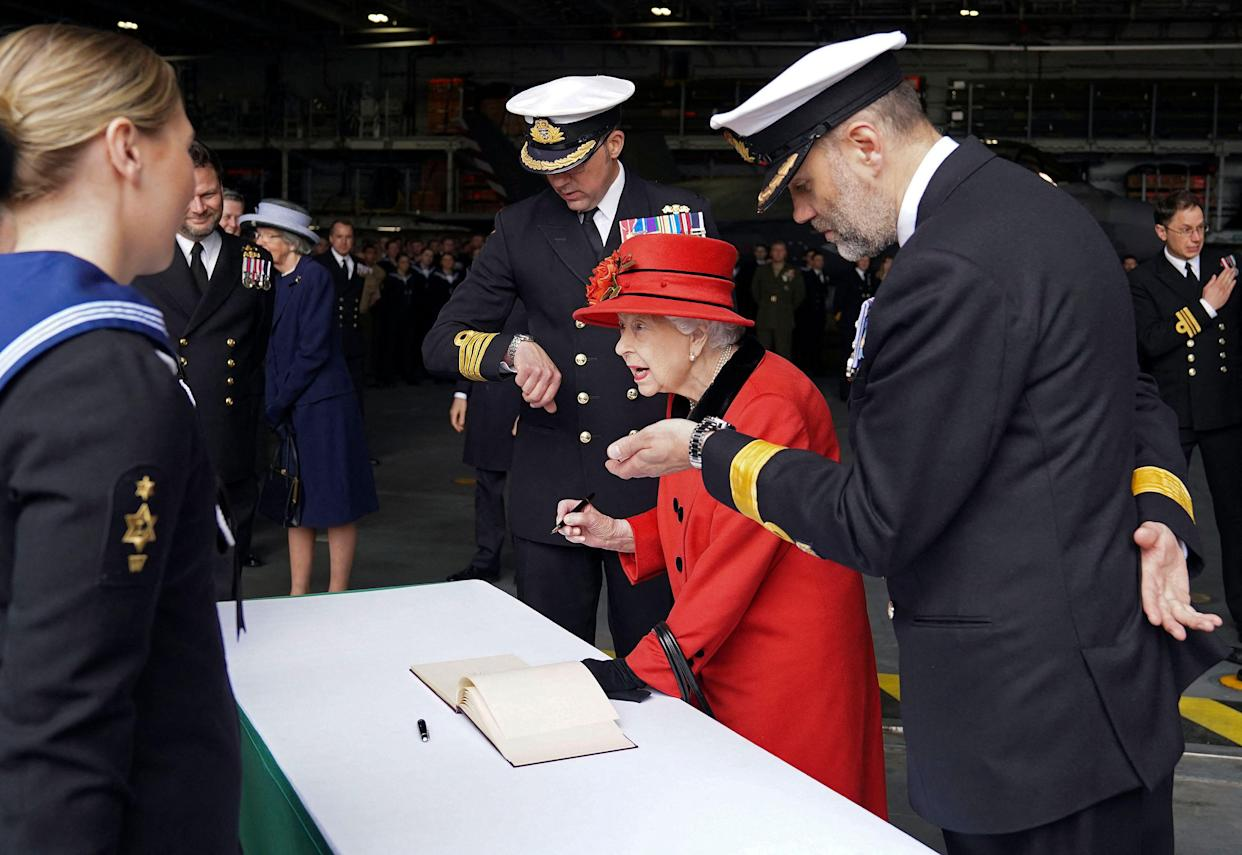 Britain's Queen Elizabeth II signs the visitors' book as is greeted by Commanding Officer Captain Angus Essenhigh (C) and Commodore Stephen Moorhouse, Commander UK Carrier Strike Group, check their watches during her visit to the aircraft carrier HMS Queen Elizabeth in Portsmouth, southern England on May 22, 2021, ahead of its maiden operational deployment to the Philippine Sea. - The aircraft carrier will embark on her first operational deployment on May 23, leading the UK Carrier Strike Group in engagements with 40 nations including India, Japan, Republic of Korea and Singapore. (Photo by Steve Parsons / POOL / AFP) (Photo by STEVE PARSONS/POOL/AFP via Getty Images)