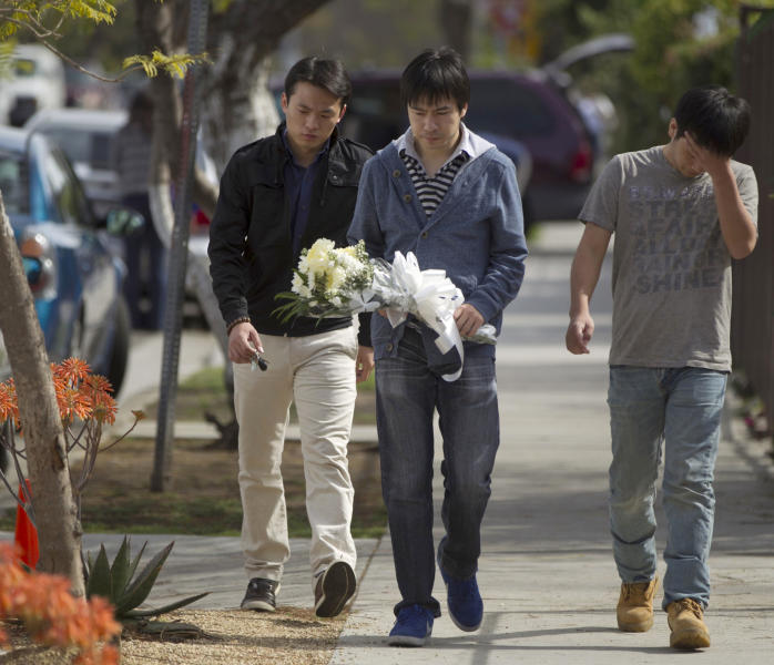 University of Southern California students bring flowers to the site of the slayings of their friends, two USC graduate students shot early Wednesday, April 11, 2012, in Los Angeles. Police said a gunman opened fire on a BMW near the University of Southern California campus on Wednesday, killing two international students from China in what may have been a bungled carjacking attempt. (AP Photo/Damian Dovarganes)