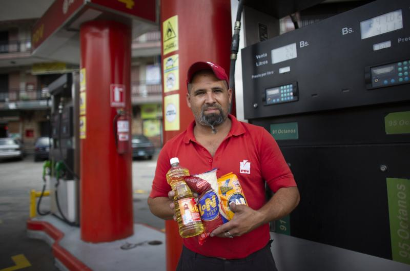 In this Oct. 8, 2019 photo, gas station attendant Leowaldo Sanchez poses with food items he was paid with by motorists: a bottle of cooking oil, a kilogram if rice and a package of corn flour, as he works at the pump in San Antonio de los Altos on the outskirts of Caracas, Venezuela. Bartering at the pump has taken off as hyperinflation makes Venezuela's paper currency, the bolivar, hard to find and renders some denominations all but worthless, so that nobody will accept them. (AP Photo/Ariana Cubillos)