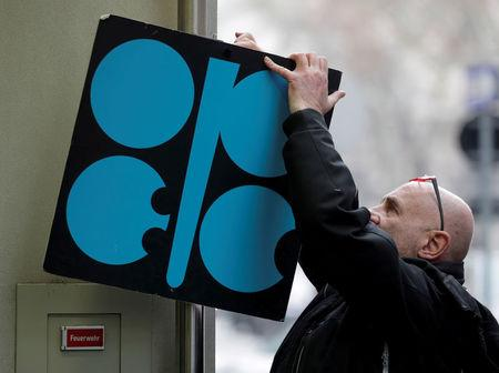 FILE PHOTO: A man fixes a sign with OPEC's logo next to its headquarters in Vienna