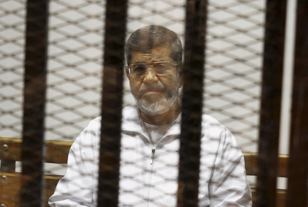 FILE - In this May 8, 2014 file photo, Egypt's ousted Islamist President Mohammed Morsi sits in a defendant cage in the Police Academy courthouse in Cairo, Egypt. An Egyptian court sentenced ousted President Mohammed Morsi to death, Saturday, May 16, 2015, over a 2011 mass prison break.. (AP Photo/Tarek el-Gabbas, File)