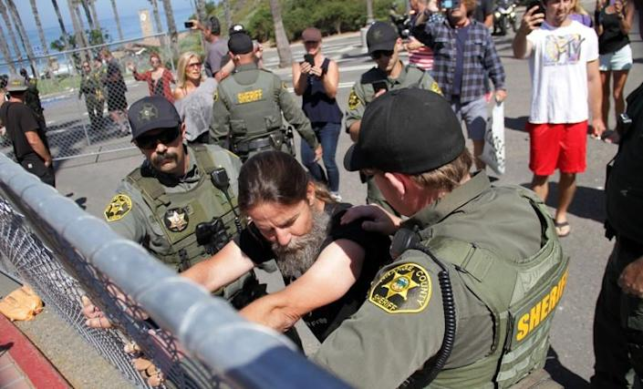 With sheriff's deputies holding him in place, Alan Hostetter clings to a fence at the Pier Bowl parking lot on May 21, 2020, as part of a rally he organized to demonstrate against the fencing around the lot.