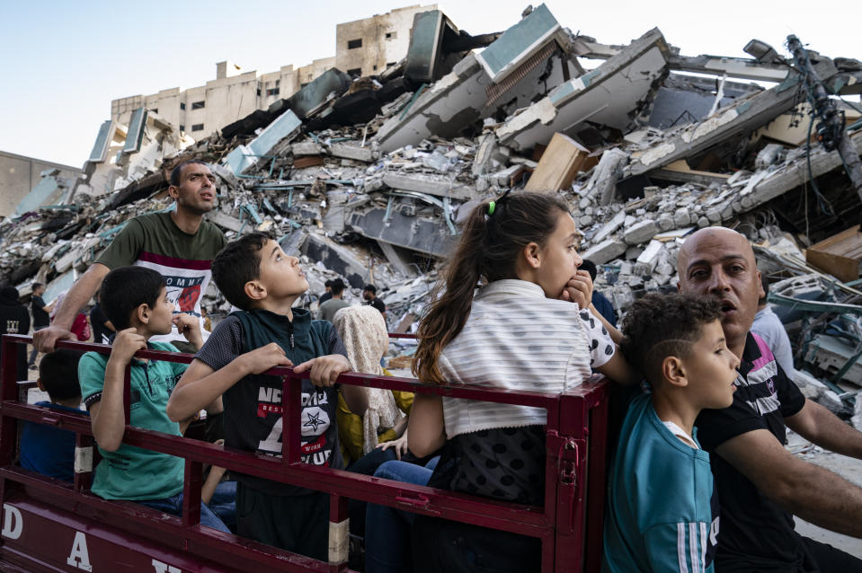 Spectators gather to view the rubble of the al-Jalaa building following a cease-fire reached after an 11-day war between Gaza's Hamas rulers and Israel, in Gaza City, Friday, May 21, 2021. The building housed the Associated Press bureau in Gaza City for 15 years. (AP Photo/John Minchillo)