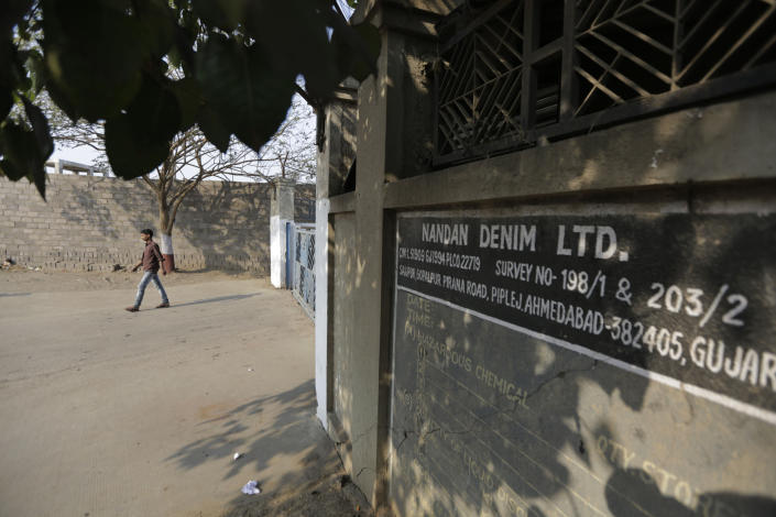 In this Tuesday, Feb. 11, 2020 photo, a man walks out from Nandan Denim garment factory, one of the largest denim suppliers in the world, where a fire broke out on Saturday in Ahmedabad, India. At least seven people died when a blaze swept a garment factory that has ties to major U.S. retailers, according to its website. Some of the U.S. and multinational companies listed on the website said they were not actually customers, and many issued statements that strongly condemned dangerous work sites. (AP Photo/Ajit Solanki)