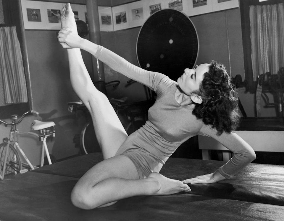 <p>Women weren't interested in defining or growing their muscles through fitness in the 1940s. This image of Ziegfeld dancer and actress Susanne Remos stretching to stay slim shows the biggest fitness trend of the decade. </p>