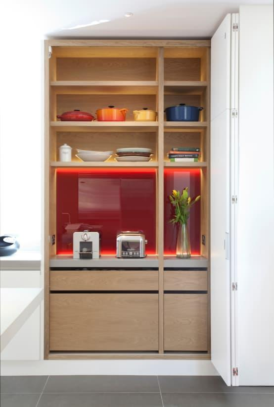 <p>Back to the kitchen – coloured glass was used as a wall cladding, both for the backsplash and inside the cabinetry, flaunting an exciting splash of red that comes alive thanks to the soft neutrals that surround it. And just notice how cleverly this design commits to keeping clutter at bay via its shelving and cubby holes.</p><p>Let's scope out a few more images that speak of this one-of-a-kind creation.</p>  Credits: homify / Kuche Design