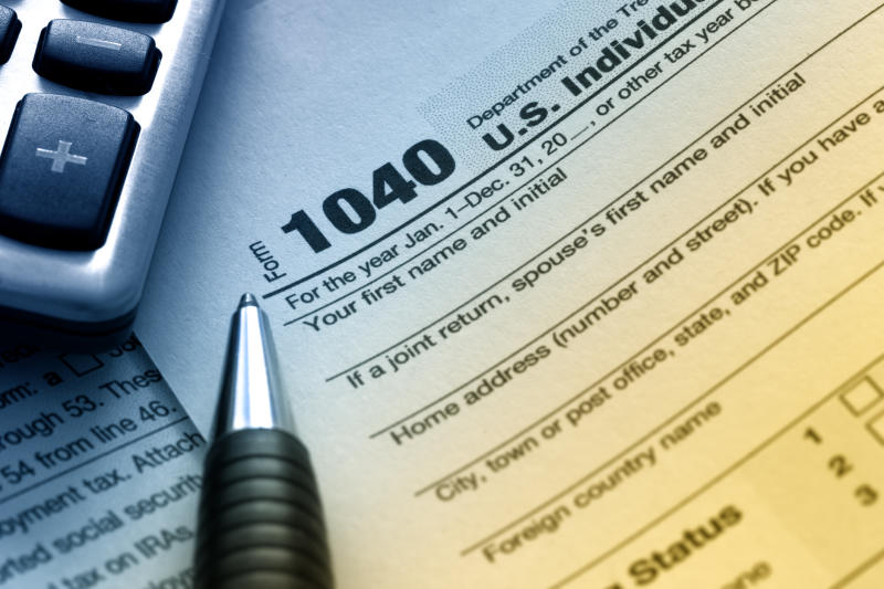 A 1040 tax form with a pen and a calculator