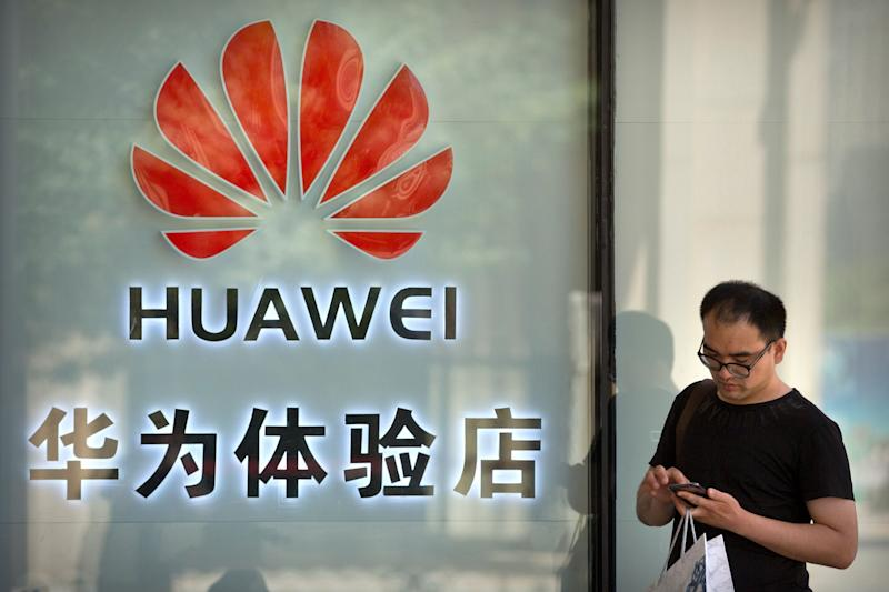 A man uses his smartphone outside of a shop selling Huawei products at a shopping mall in Beijing, Wednesday, May 29, 2019. Chinese tech giant Huawei filed a motion in U.S. court Wednesday challenging the constitutionality of a law that limits its sales of telecom equipment, the latest action in an ongoing clash with the U.S. government. (AP Photo/Mark Schiefelbein)