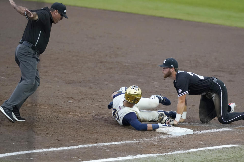 Mississippi State first baseman Luke Hancock (20) looks towards the umpire as he calls Notre Dame's Brooks Coetzee (42) safe after retrieving a passed ball during the NCAA college baseball super regional game, Sunday, June 13, 2021, in Starkville, Miss. (AP Photo/Rogelio V. Solis)