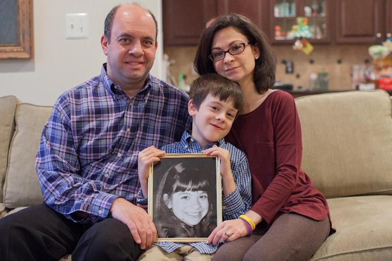 Mark Miller, left, Ellyn Miller, right, and their son Jake, center, pose while holding a photo of their daughter Gabriella, who died of brain cancer in 2013, at their home in Leesburg, Va., on Wednesday, March 12, 2014. The Senate passed a bill, named for Gabriella, Tuesday that directs $126 million over the coming decade for childhood cancer research. (AP Photo/Zach Gibson)