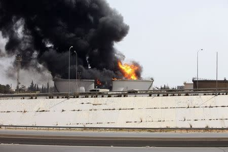 A general view shows fire burning at a fuel depot near the airport road in Tripoli