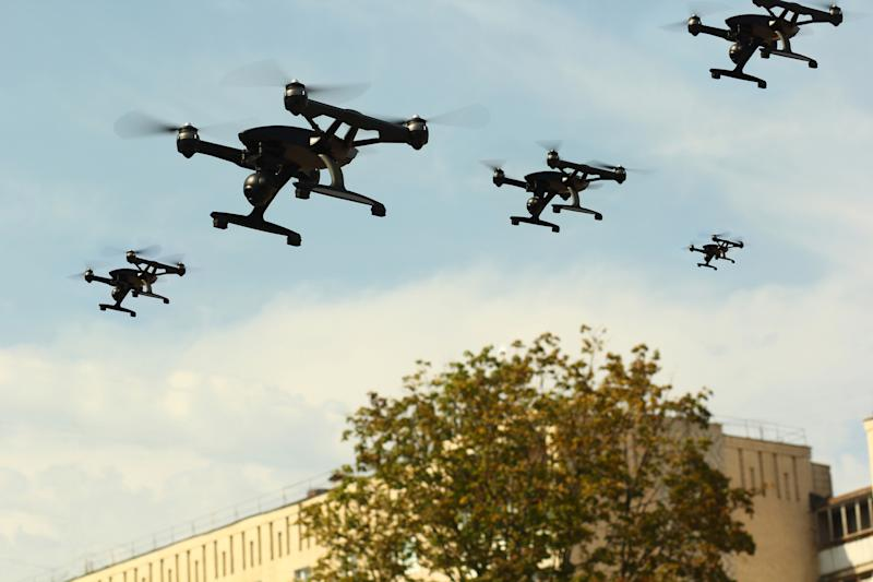 Drones fly over a building