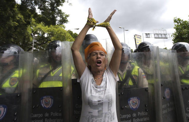 <p>A woman protests in front of a line of Bolivarian National Police during an opposition demonstration in Caracas, June 7, 2016. (AP/Ariana Cubillos) </p>