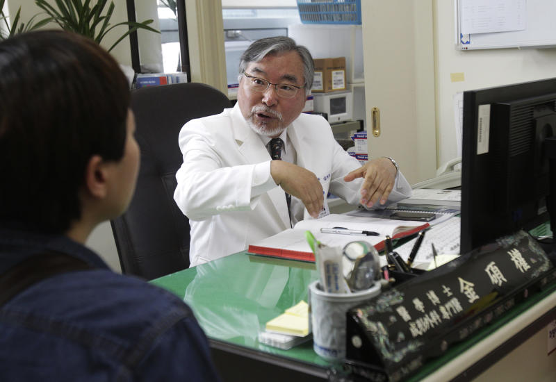 """In this March 18, 2014 photo, Dr. Kim Seok-Kwun, 61, talks with an unidentified patient at Dong-A University Hospital in Busan, South Korea. Dr. Kim is a pioneer in slowly changing views on sexuality and gender in the country, where many have long considered even discussions of sexuality a taboo. As Dr. Kim begins what will be 11 hours of surgery meant to create a functioning penis for a Buddhist nun, he is well aware of the unease his work creates in this deeply conservative country. The devout Protestant known as the """"father of South Korean transgender people"""" once wrestled with similar feelings. """"I've decided to defy God's will,"""" Kim said in an interview before the nun's recent successful surgery to become a man. (AP Photo/Ahn Young-joon)"""