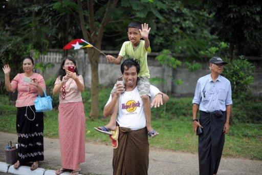 <p>Local residents wave as US President Barack Obama's motorcade drives past in Yangon. Miles of smiles lit up shabby Yangon Monday during a visit by Obama, a striking contrast to the wrenching, dark years under a xenophobic junta.</p>