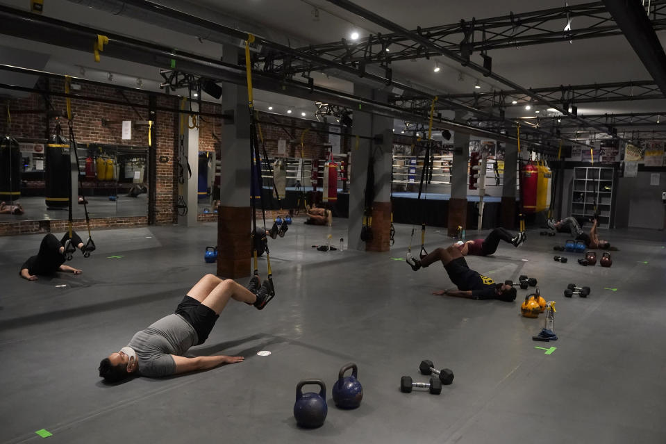 People wear masks while working out in social distancing spaces in an indoor class at a Hit Fit SF gym amid the coronavirus outbreak in San Francisco, Tuesday, Nov. 24, 2020. (AP Photo/Jeff Chiu)
