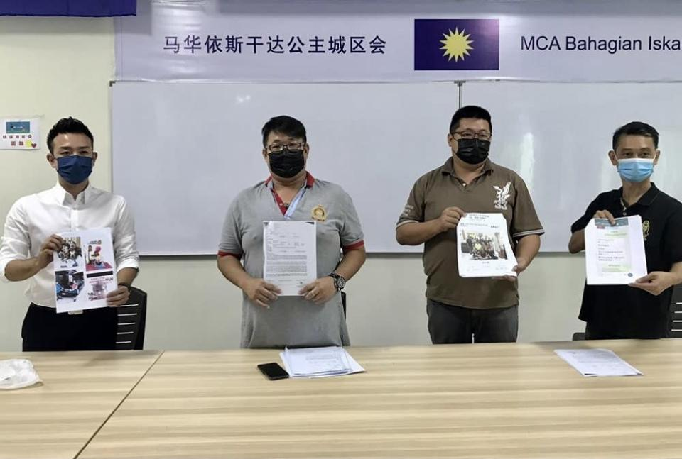 Trader Ng Chen Yuan (second, left) shows the police reports that he lodged during a media conference at the Gelang Patah MCA division office in Iskandar Puteri May 18, 2021. — Picture by Ben Tan