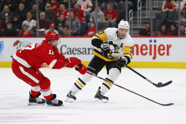 Pittsburgh Penguins defenseman Jack Johnson (3) passes the puck past Detroit Red Wings defenseman Filip Hronek (17) in the first period of an NHL hockey game Saturday, Dec. 7, 2019, in Detroit. (AP Photo/Paul Sancya)