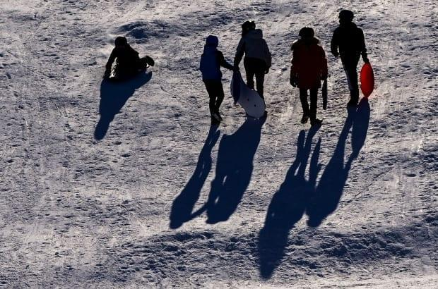 Tobogganers cast long shadows down the slope at Ottawa's Lansdowne Park on Feb. 4, 2021.