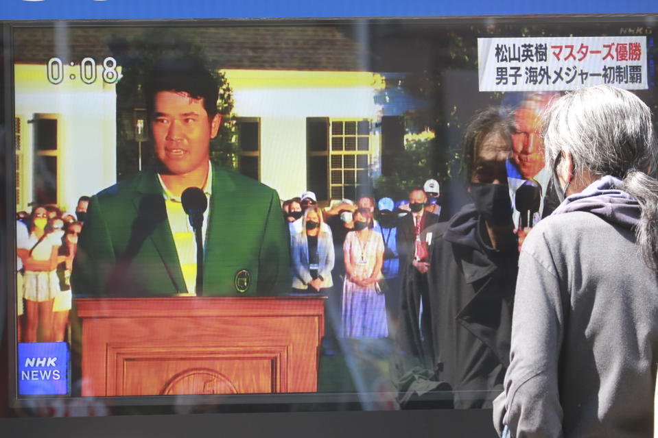 A passerby watches a tv news report showing Japanese golfer Hideki Matsuyama in the Masters, in Tokyo, Monday, April 12, 2021. From Japan's prime minister on down, the country celebrated Matsuyama's victory in the Masters — the first Japanese to win at Augusta National and wear the famous green jacket.(AP Photo/Koji Sasahara)