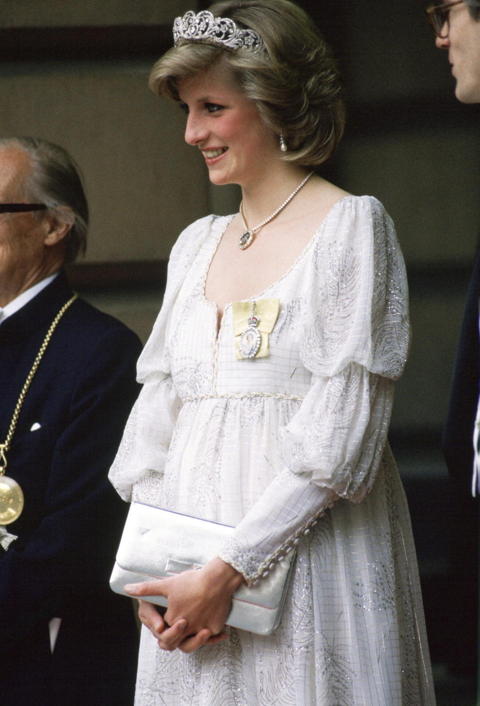 <p>While pregnant with Prince Harry, Princess Diana wears a bohemian-style white maternity dress with the Spencer family tiara and a diamond necklace in the shape of the Prince of Wales' ostrich feathers for an event at the Royal Academy. (Photo: Getty Images) </p>