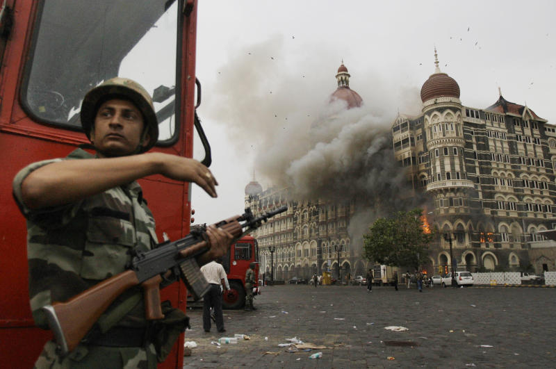 FILE - In this Nov. 29, 2008, file photo, an Indian soldier takes cover as the Taj Mahal hotel burns during gun battle between Indian military and militants inside the hotel in Mumbai, India. A Chicago businessman convicted of supporting terrorist groups has been arrested in Los Angeles to face charges in India for attacks in Mumbai in 2008 that killed more than 160 people. Federal prosecutors said Friday, June 19, 2020, that Tahawwur Rana, a Pakistani-born Canadian, was arrested after winning an early release from a Los Angeles federal prison because of coronavirus. (AP Photo/David Guttenfelder)