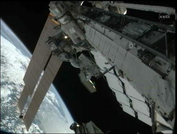 Japanese spacewalker Akihiko Hoshide is pictured holding a failed power switching unit during a spacewalk on Aug. 30, 2012. In the photo, Hoshide is riding on the end of the space station's robotic arm.