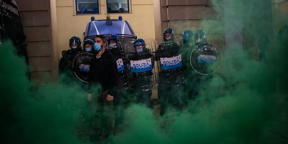 Demonstrators clash with Riot Police during the protest against the lockdown in Piazza Castello on October 26, 2020 in Turin, Italy. The protest is organized to protest against the blockade to restaurant and bars and curfew imposed in the Piedmont Region and by the Italian Government of the evening lockdown which will start from today at 6pm to contain the coronavirus pandemic. (Photo by Mauro Ujetto/NurPhoto via Getty Images)