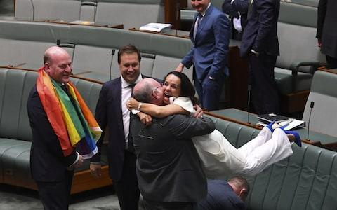 Liberal MP Warren Entsch lifts up Labor MP Linda Burney as they celebrate the passing of the Marriage Amendment Bill - Credit: REUTERS